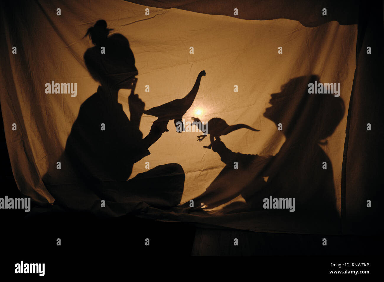 Silhouette of woman with kid playing behind sheet - Stock Image