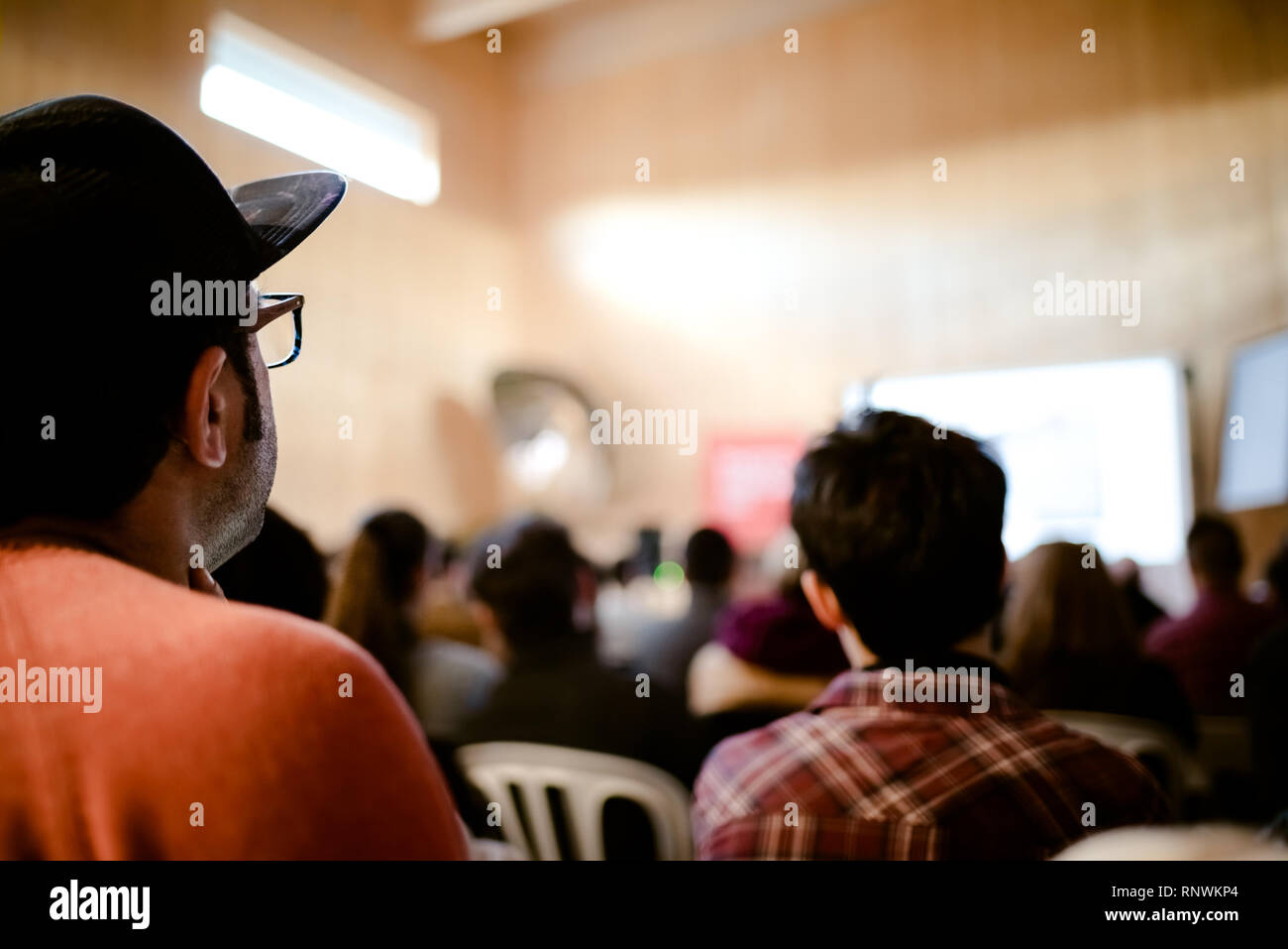 Young people attending a business conference meeting, unfocused background. - Stock Image