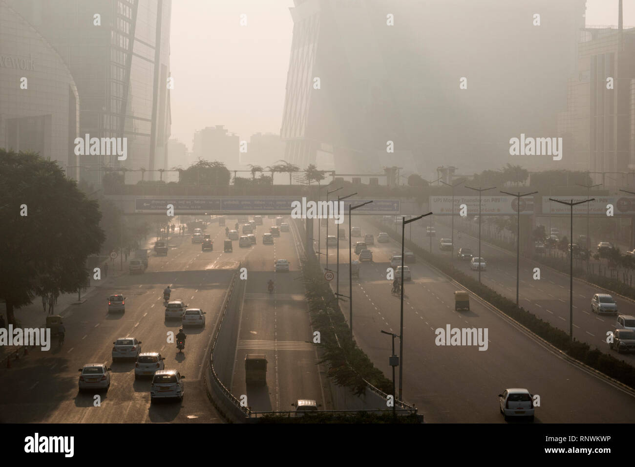 Traffic and pedestrians in hazardous levels of air pollutioN in Cyber City, Gurugram, India - Stock Image