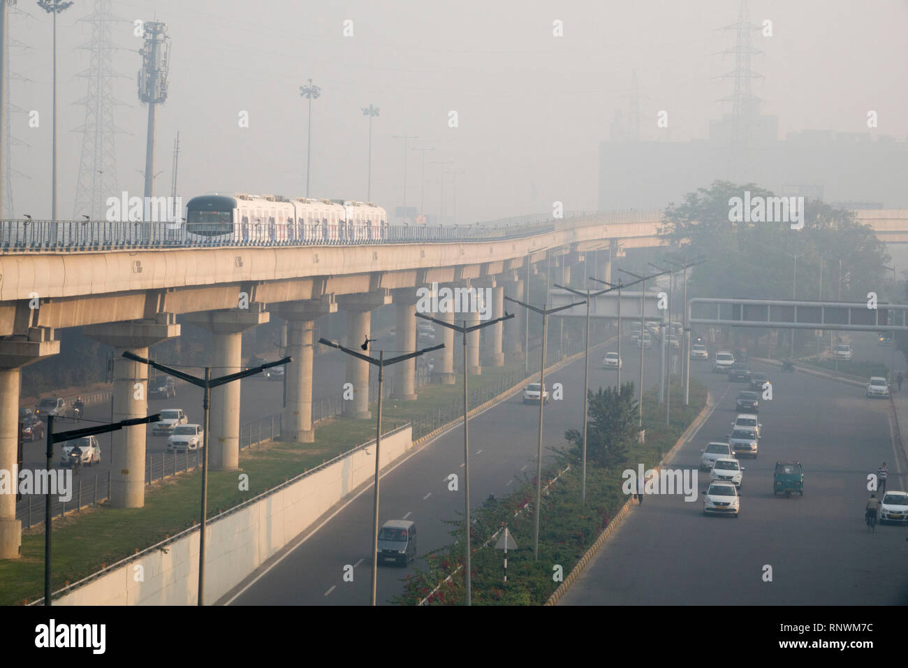Metro train and traffic in hazardous levels of air pollution in Cyber City, Gurugram, India - Stock Image