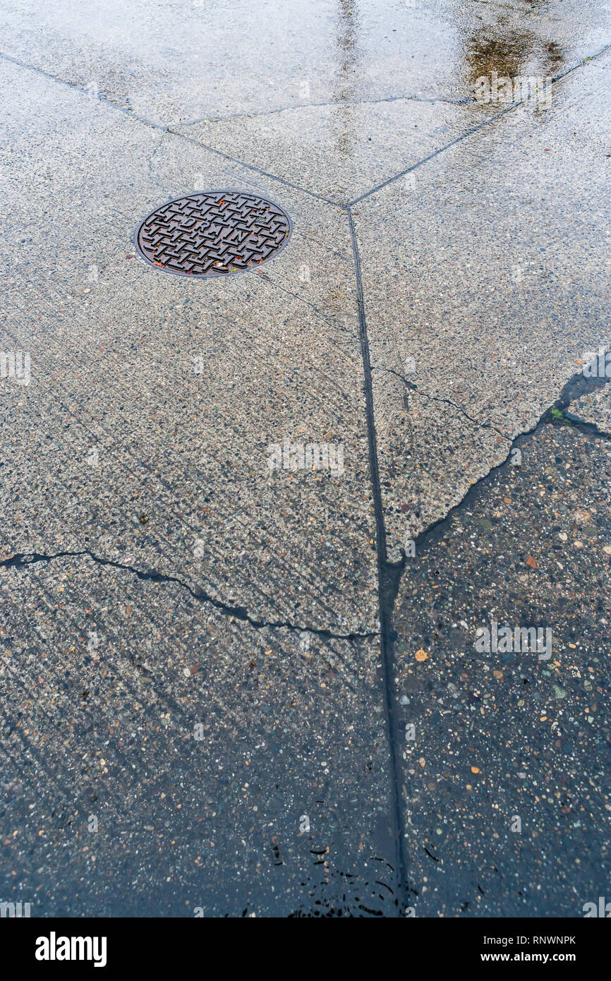 A detail shot of a concrete street and a manhole cover during a rain storm. - Stock Image