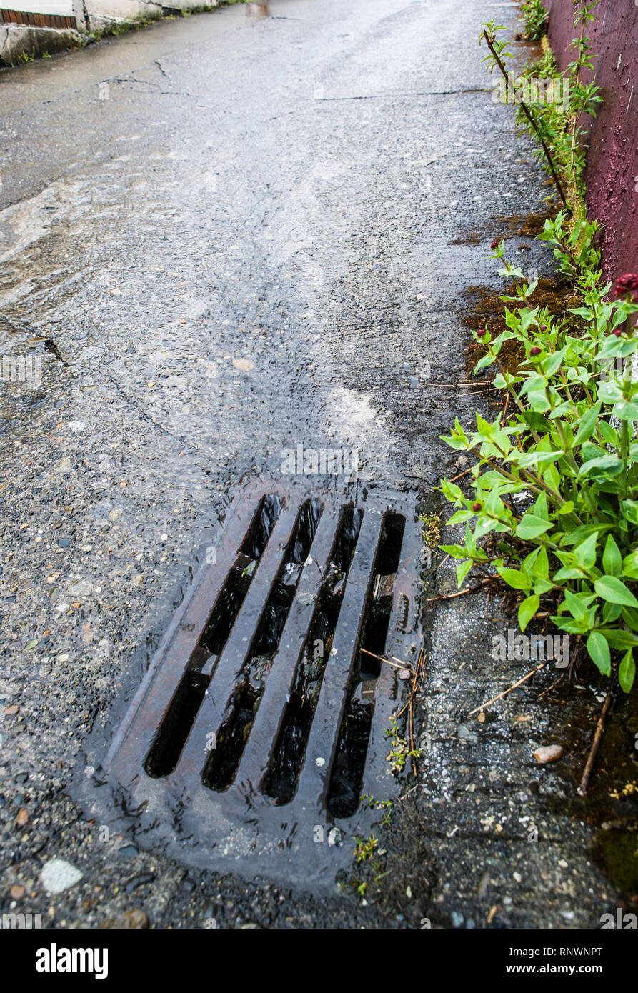 Water flowing down a street to a storm drain on a rainy day. - Stock Image