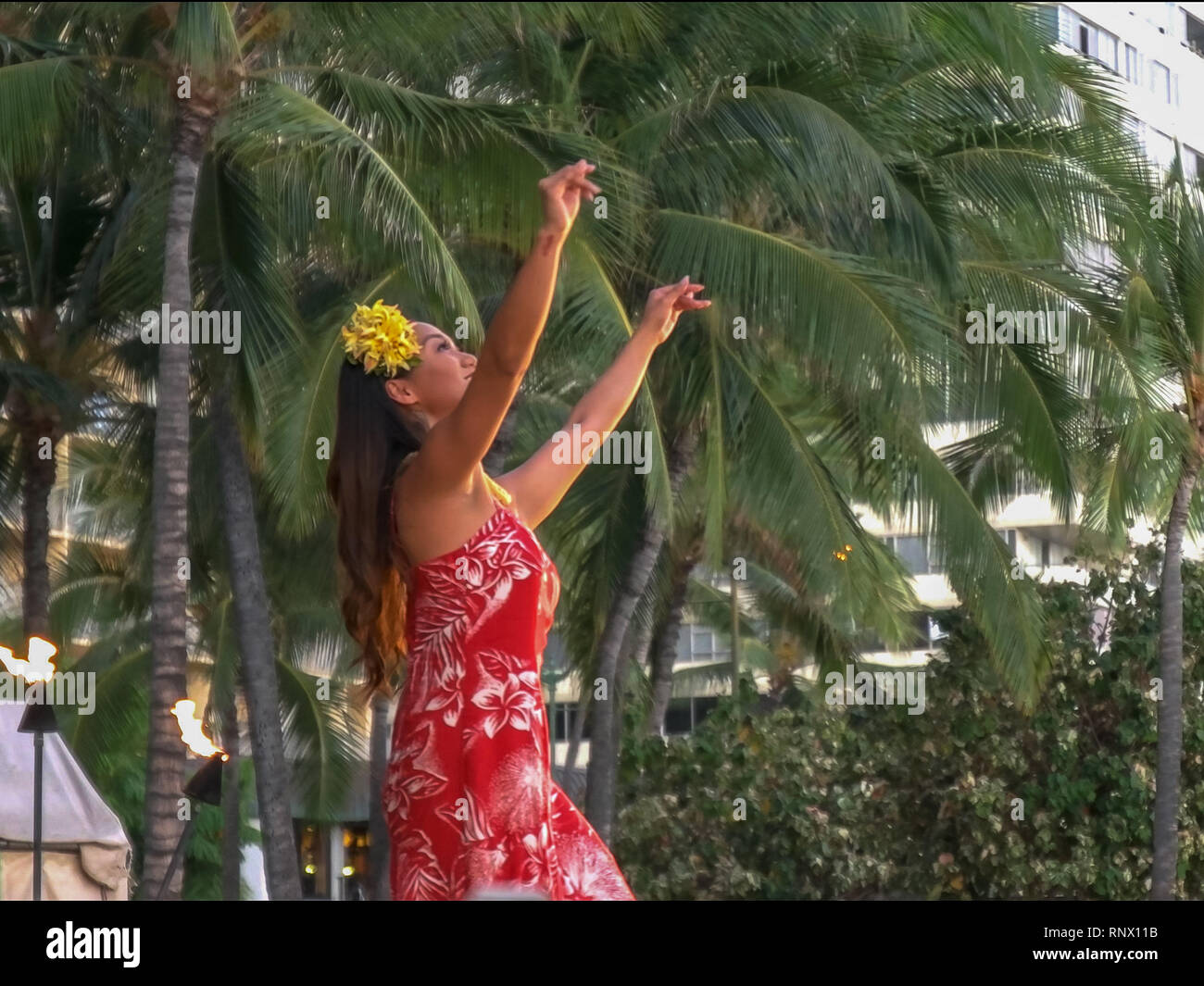 WAIKIKI, UNITED STATES OF AMERICA - AUGUST 6 2015: a female hula dancer in a red dress performing at waikiki - Stock Image