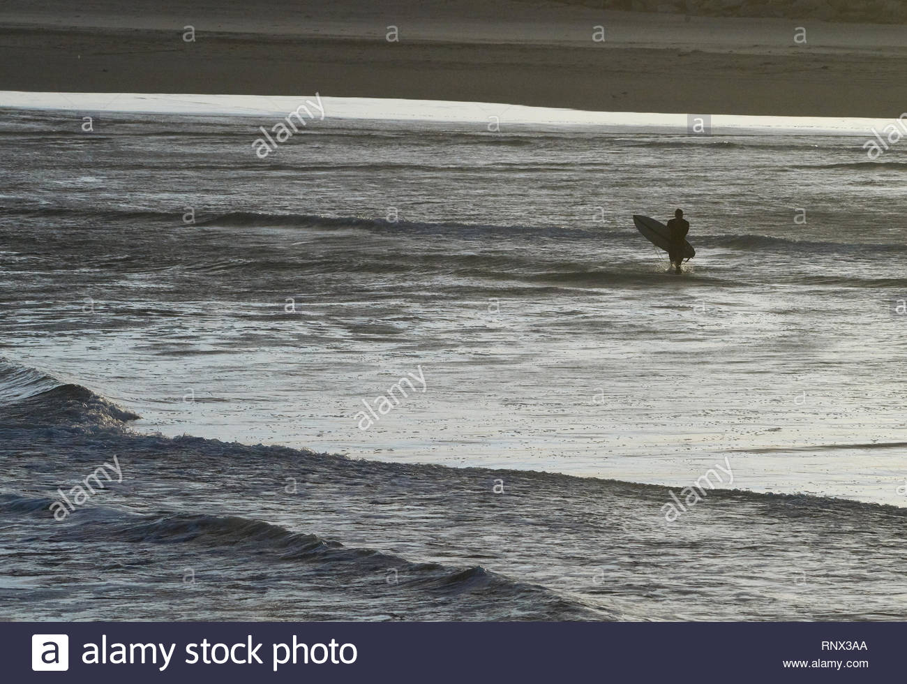 Yamba, NSW / Australia. An image depicting  the silhouette of a lone surfer entering the Pacific Ocean; taken using a telephoto lens looking onshore. - Stock Image