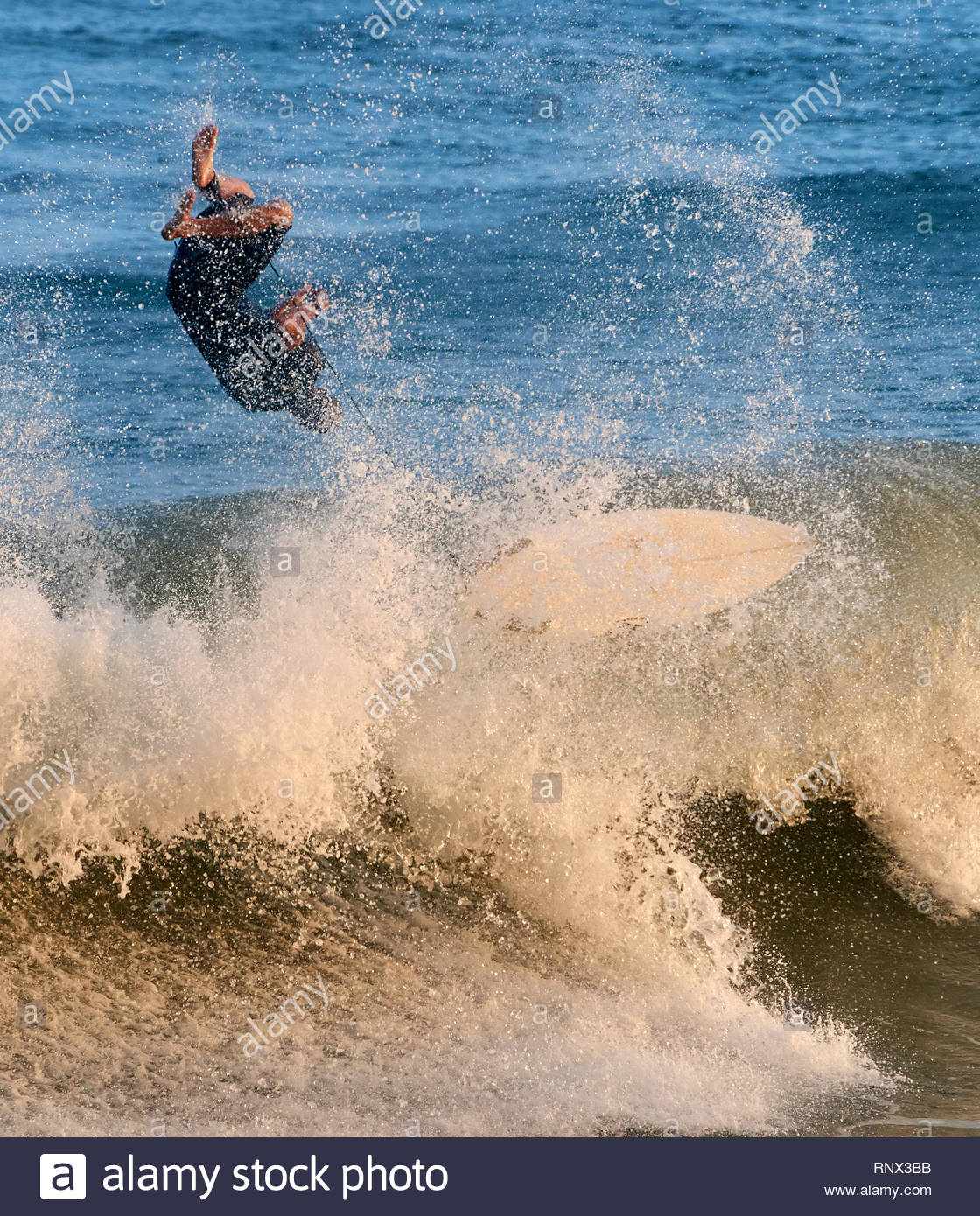 A male surfer, upside-down in the air, as he playfully ejects himself off a closing out wave; at Turners Beach, Yamba, NSW, Australia. - Stock Image
