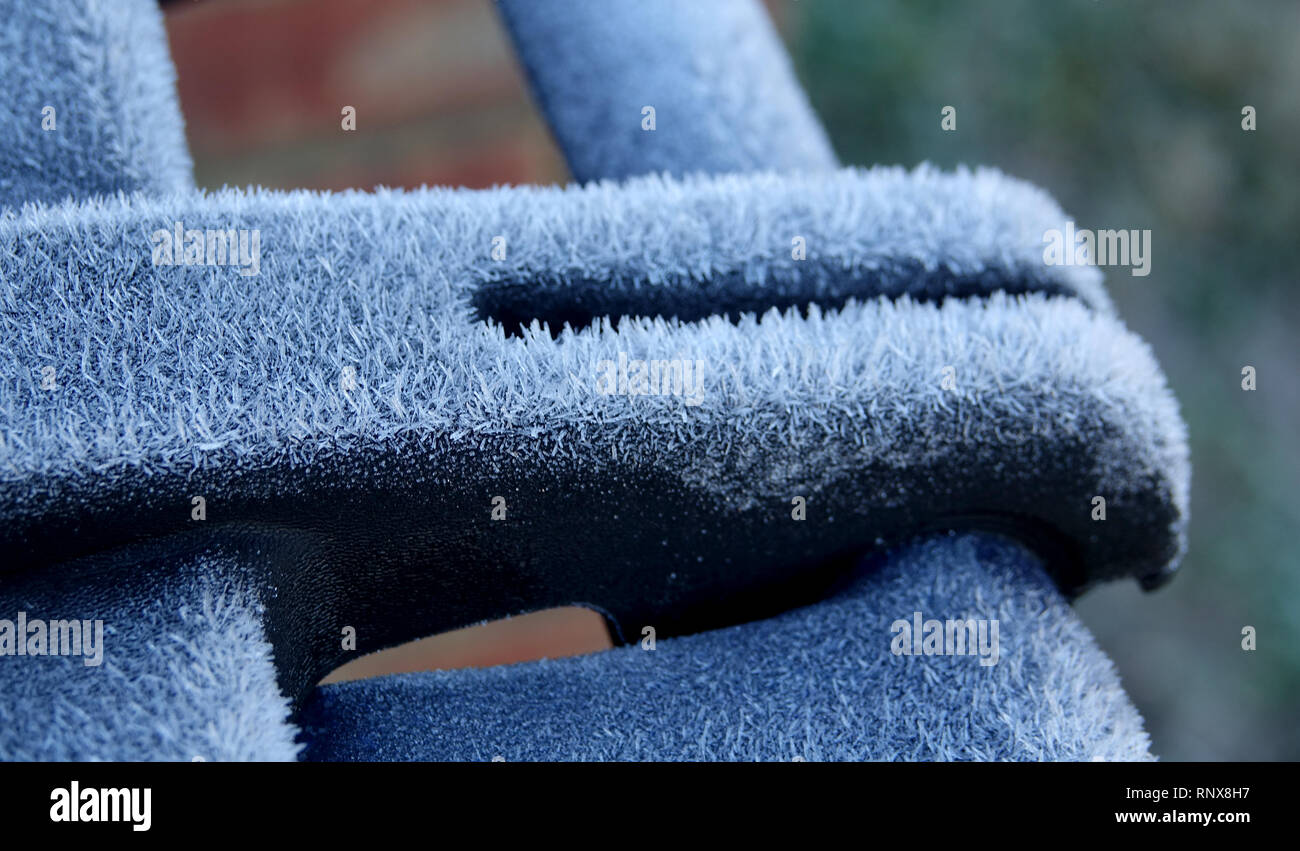 Hoar frost appears to resemble a feathery grayish-white crystalline deposit of water vapor on a plastic container - Stock Image