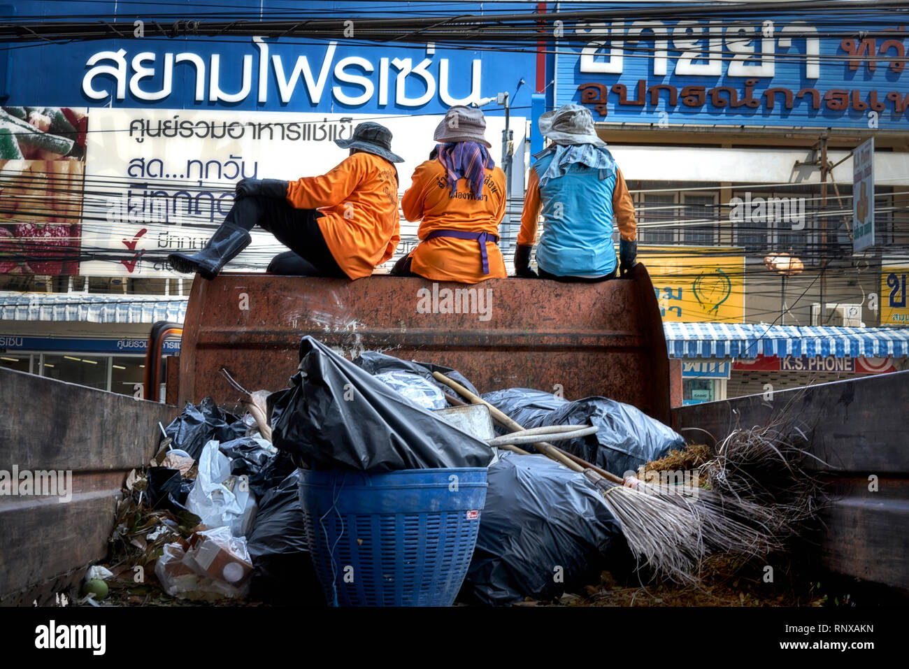 Rubbish collection. Female Thai road sweepers sat atop the refuge collection truck. Thailand, Southeast Asia - Stock Image