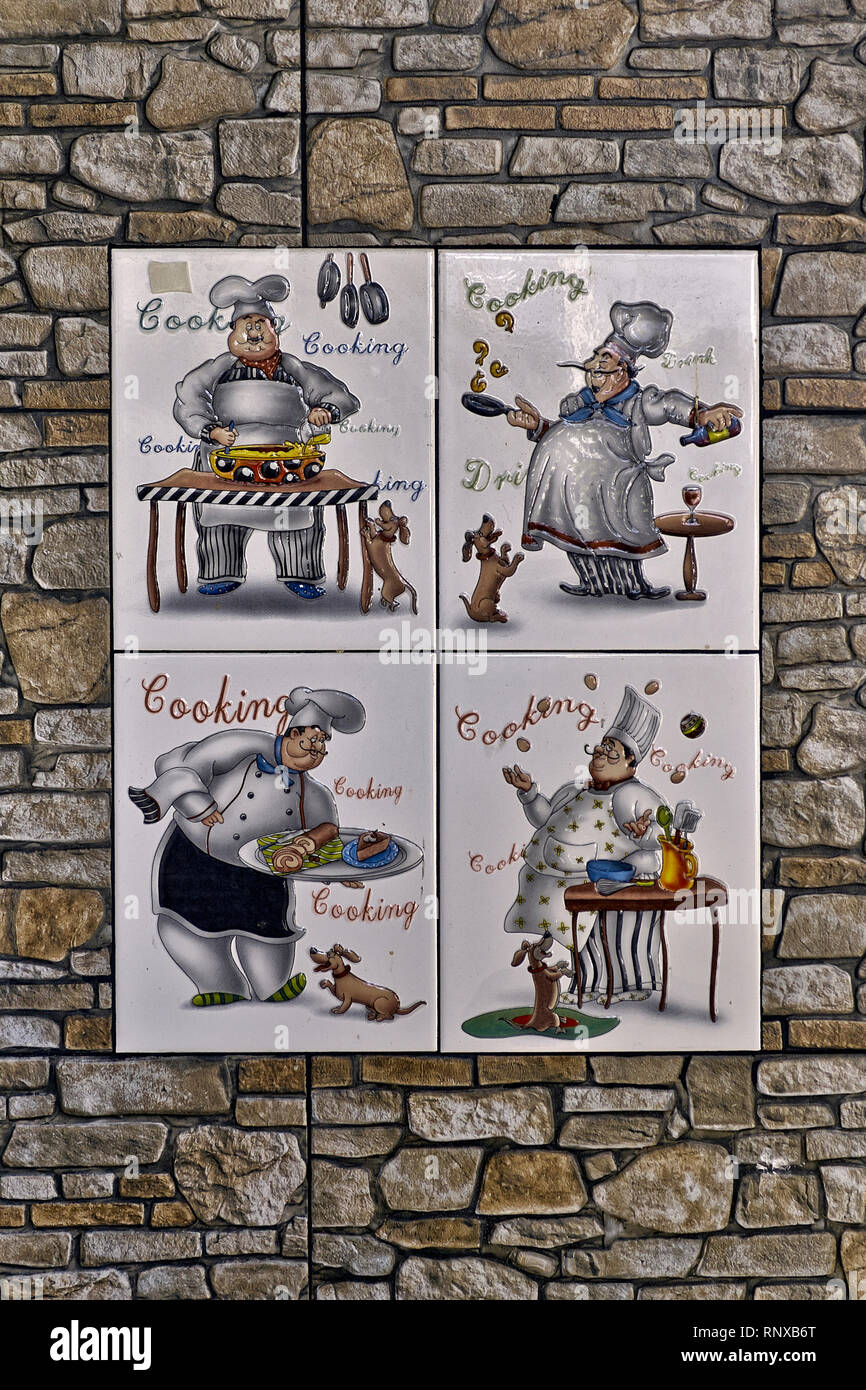 Wall tile. Ceramic tiles on a restaurant exterior wall featuring chefs cooking - Stock Image
