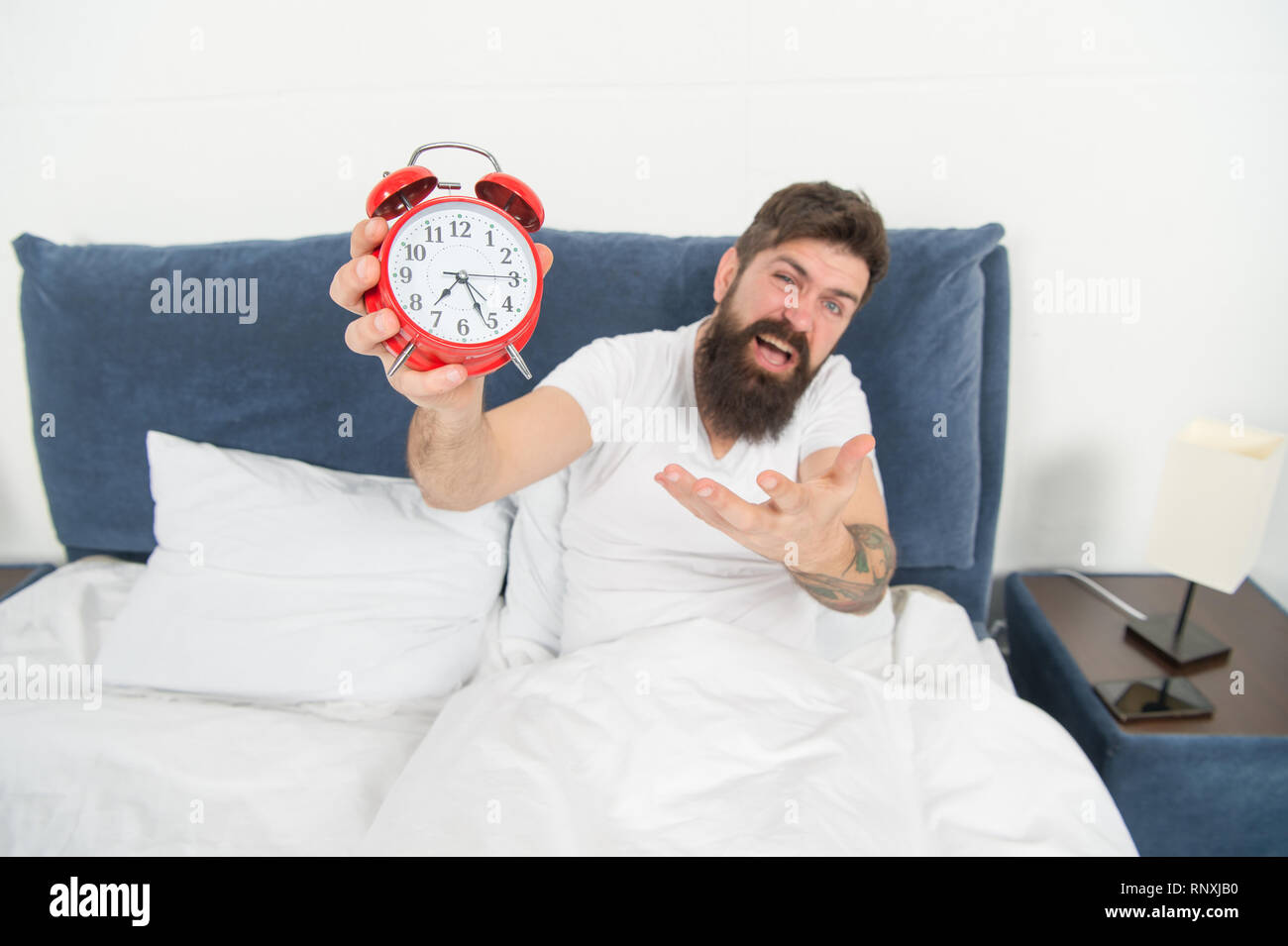 Problem with early morning awakening. Get up with alarm clock. Overslept again. Tips for waking up early. Tips for becoming an early riser. Man bearded hipster sleepy face in bed with alarm clock. - Stock Image