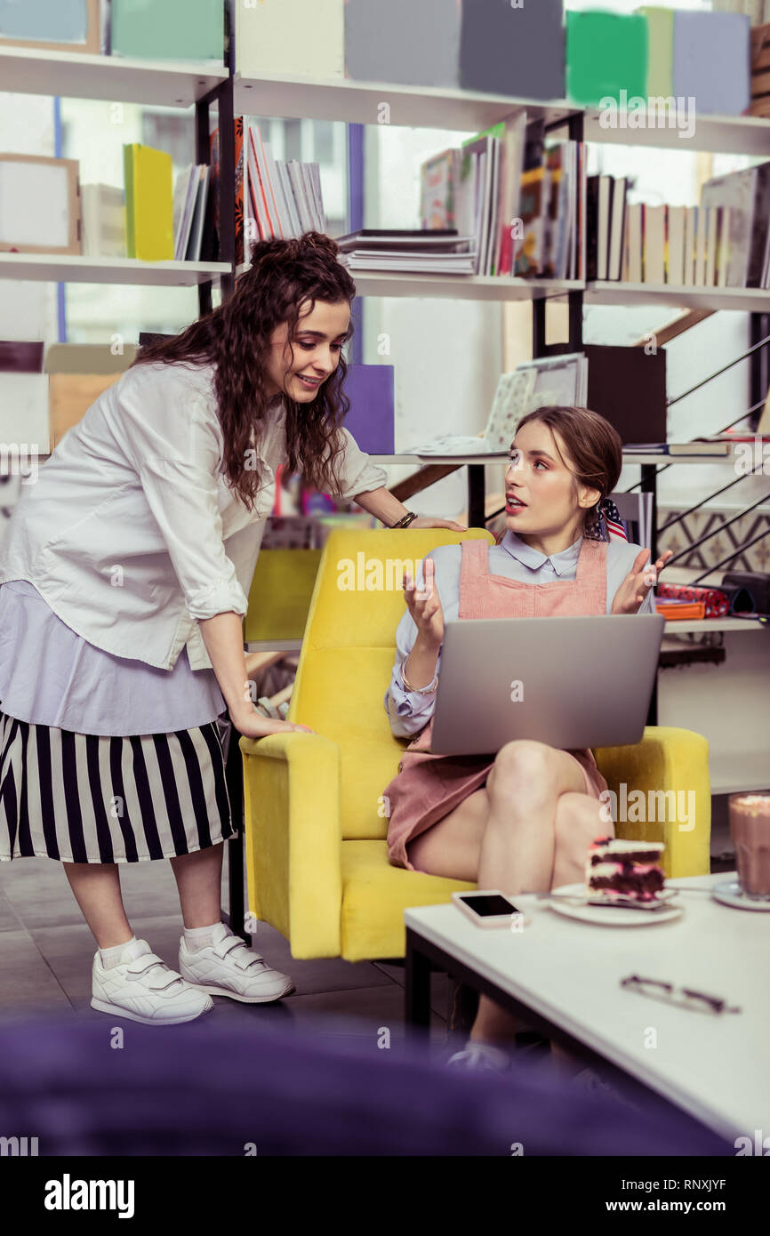 Serious light-haired girl explaining her work to curious friend - Stock Image