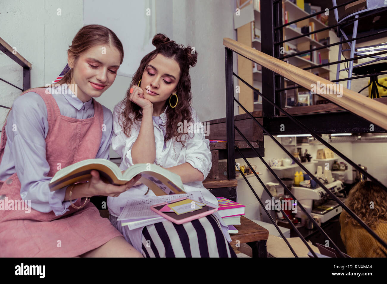 Calm and peaceful girls sitting shoulder to shoulder and reading book - Stock Image