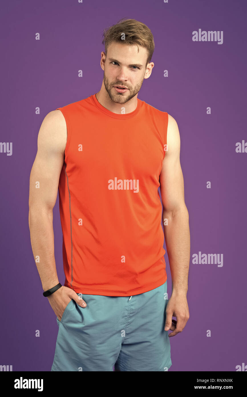 Athlete on violet background. Muscular man in orange vest and blue shorts, sportswear fashion. Fit and confident. Sport fashion for training and workout. Fitness and wellness. - Stock Image