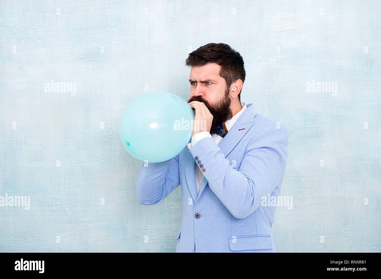 Man inflating a blue balloon. Bearded man with balloon. Happy birthday. preparation to party, celebration. Praparation to birthday party. Birthday party balloon. Party balloon. stylish event manager. - Stock Image