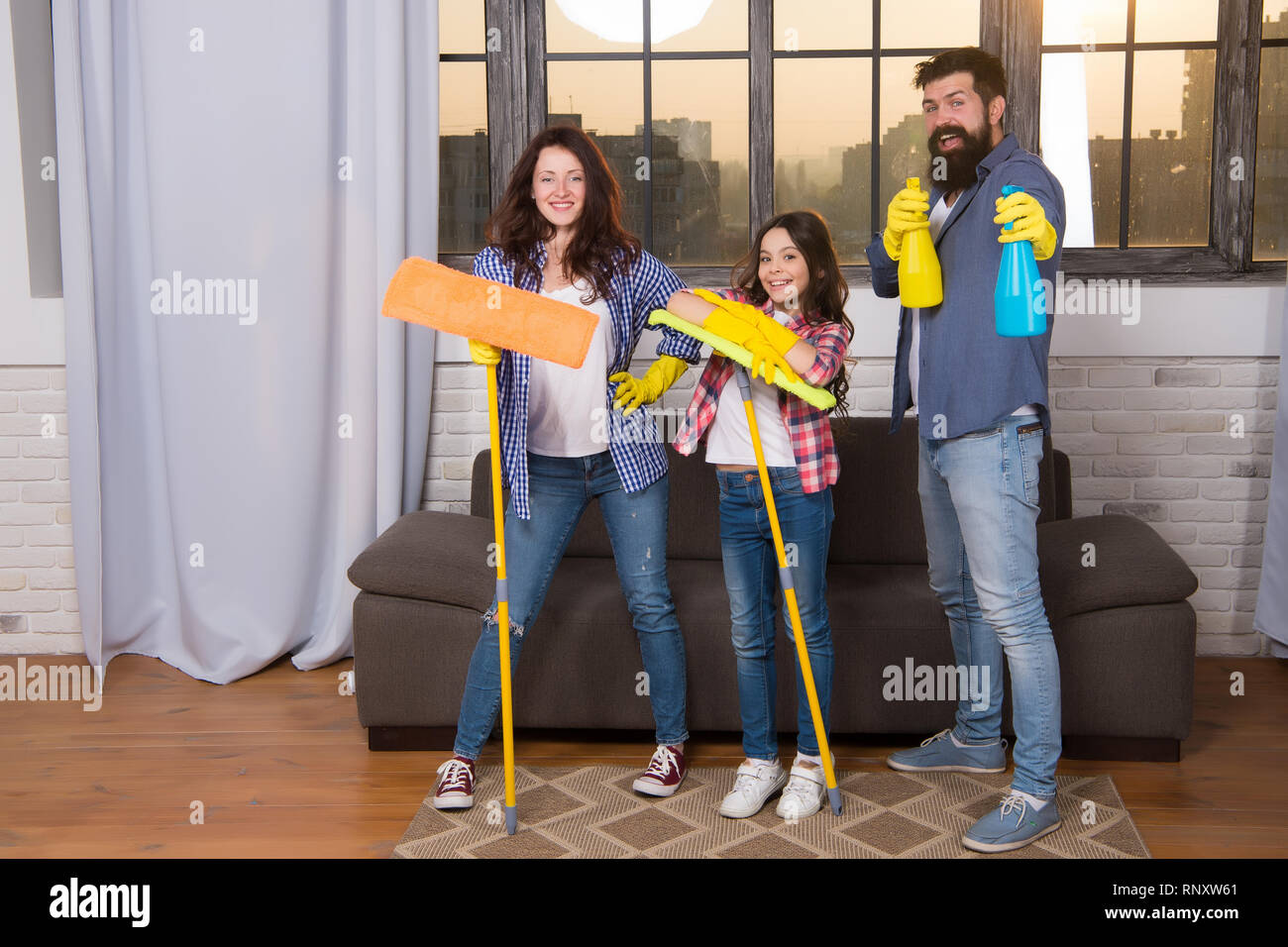 Cleaning day. Family mom dad and daughter with cleaning supplies at living room. We love cleanliness and tidiness. Cleaning together easier and more fun. Family care about cleanliness. Start cleaning. - Stock Image