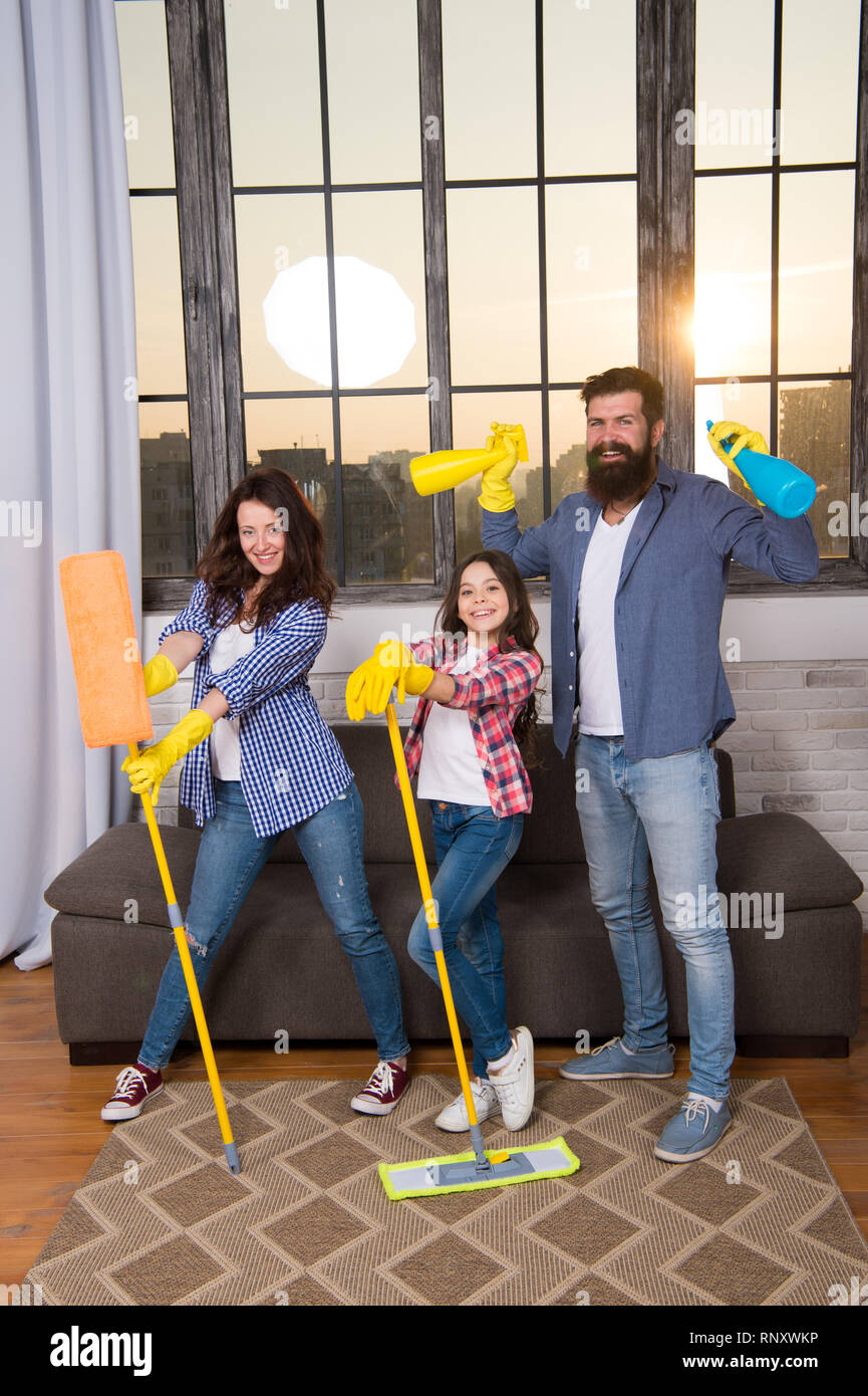 Family mom dad and daughter with cleaning supplies at living room. We love cleanliness and tidiness. Cleaning together easier and more fun. Family care about cleanliness. Start cleaning. Cleaning day. - Stock Image