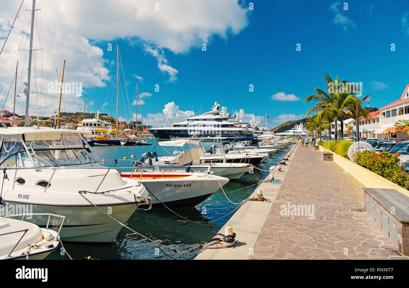 Gustavia, st.barts - January 25, 2016: boats and yachts anchored at sea pier on tropical beach. Yachting and sailing. Luxury travel on boat. Summer vacation on island. Water transport and vessel. - Stock Image