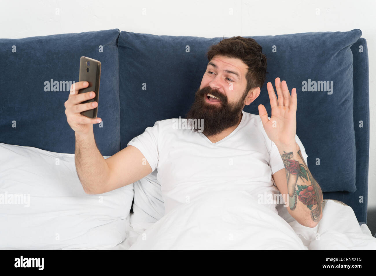 First thing in morning. Man bearded hipster surfing internet social networks. Say hello to friends. Online communication. Mobile dependence. Social networks communication. Digital communication. - Stock Image