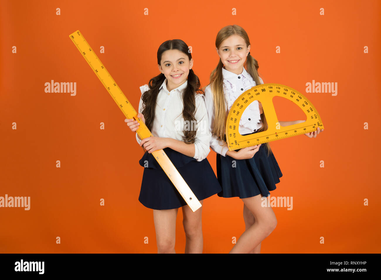 Education and school concept. School students learning geometry. Kids school uniform on orange background. STEM school disciplines. Pupil cute girls with big rulers. Geometry favorite subject. - Stock Image