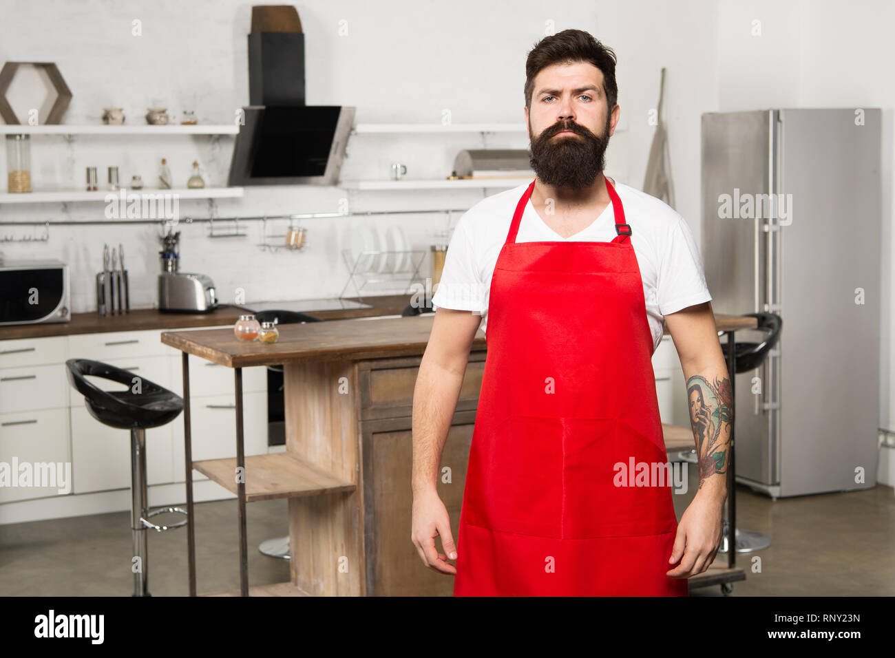 Ready to work. Man chef cooking. Mature male. Bearded man cook. Restaurant or cafe cook. Hipster in kitchen. Bearded man in red apron. Male chef in white uniform. Professional chef in kitchen. - Stock Image