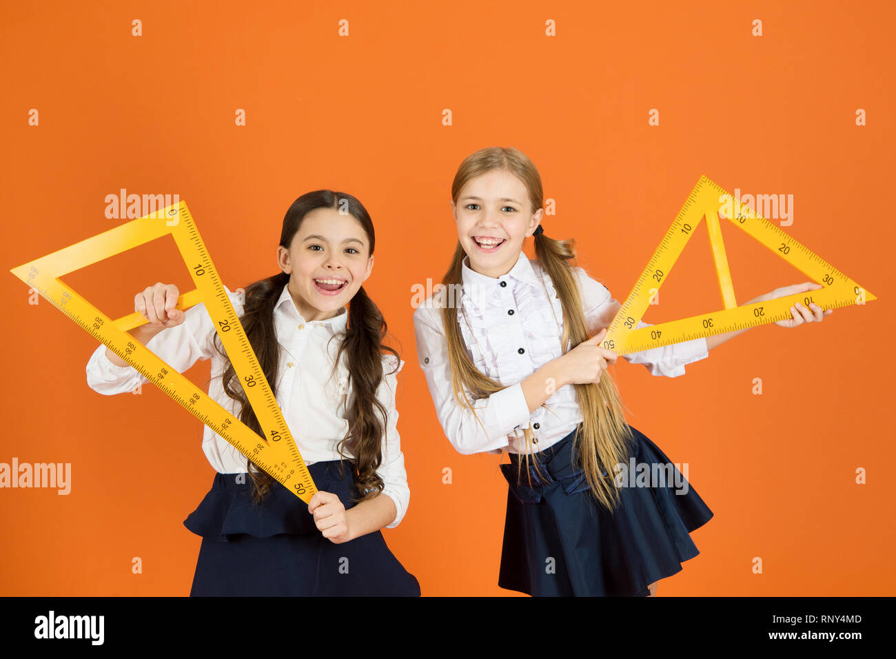 Kids school uniform on orange background. Pupil cute girls with big rulers. Geometry school subject. Drawing with ruler chalkboard. Education and school concept. School students learning geometry. - Stock Image