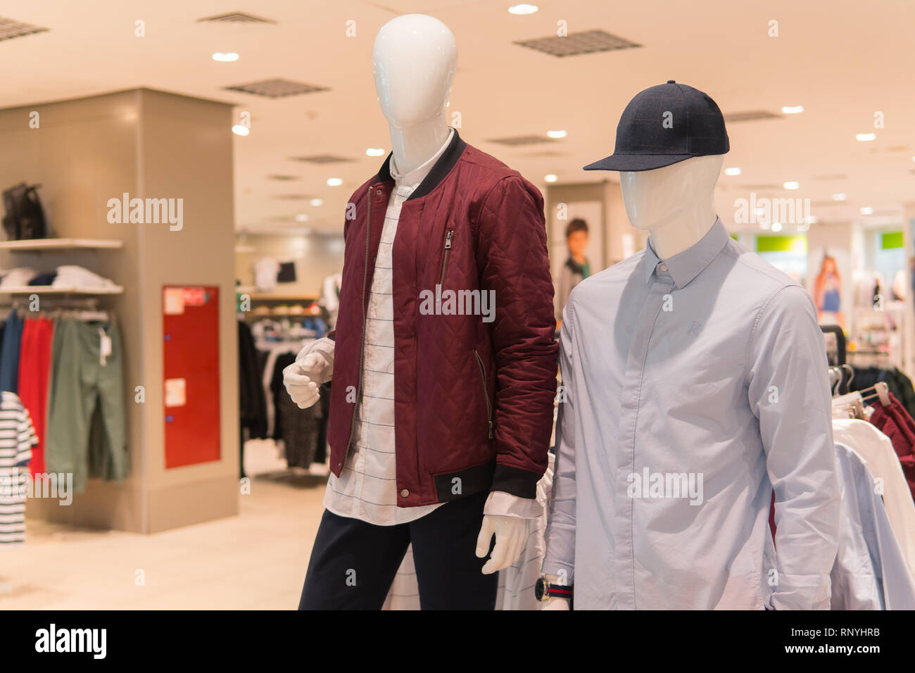 af8ec217071 Male mannequins in red jacket, gray shirt and black baseball cap. Fashion  store interior on background. Clothing shop, nobody
