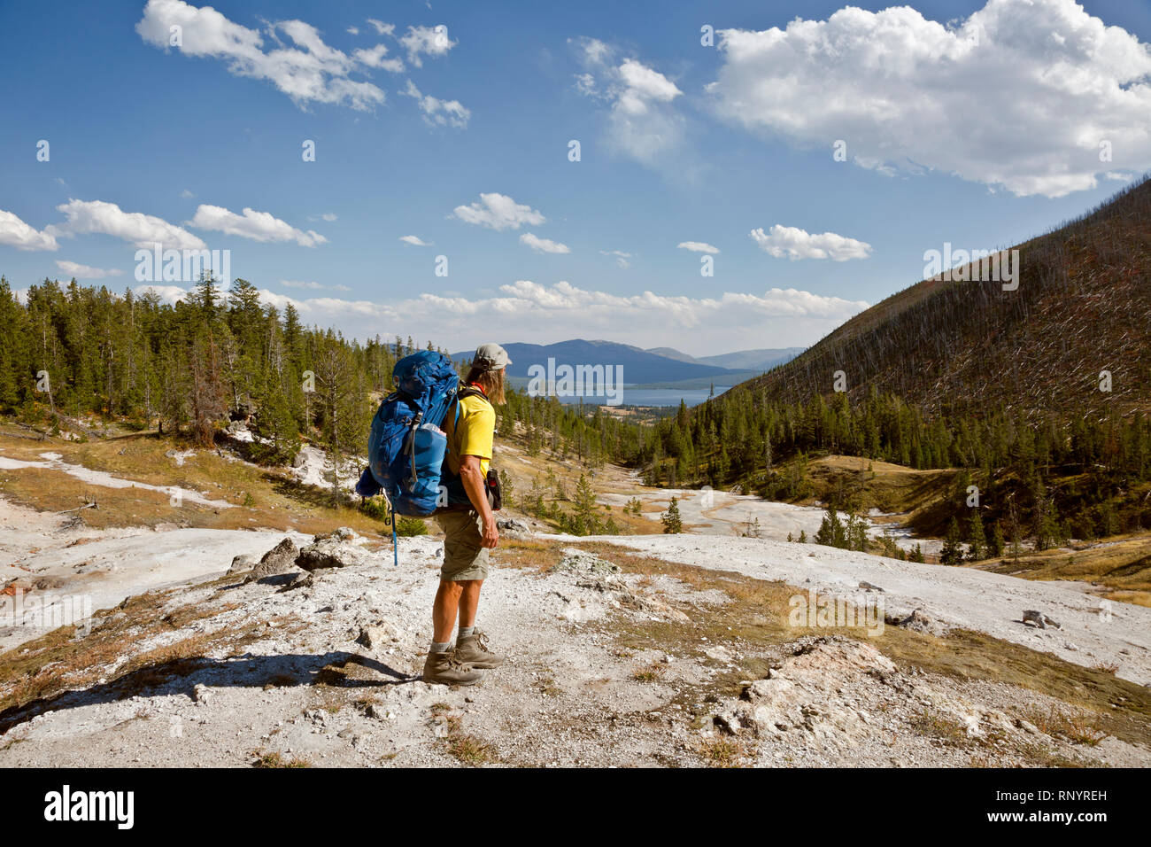 WY03815-00...WYOMING - Hiker at one of the thermal areas along the trail to Heart Lake and the Heart Lake Geyser Basin in Yellowstone National Park. - Stock Image
