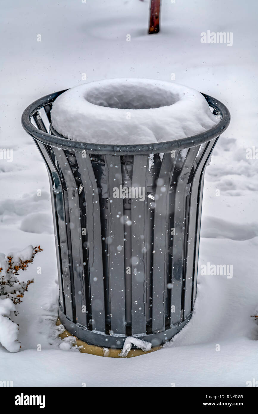 Garbage can on snow covered ground in winter - Stock Image