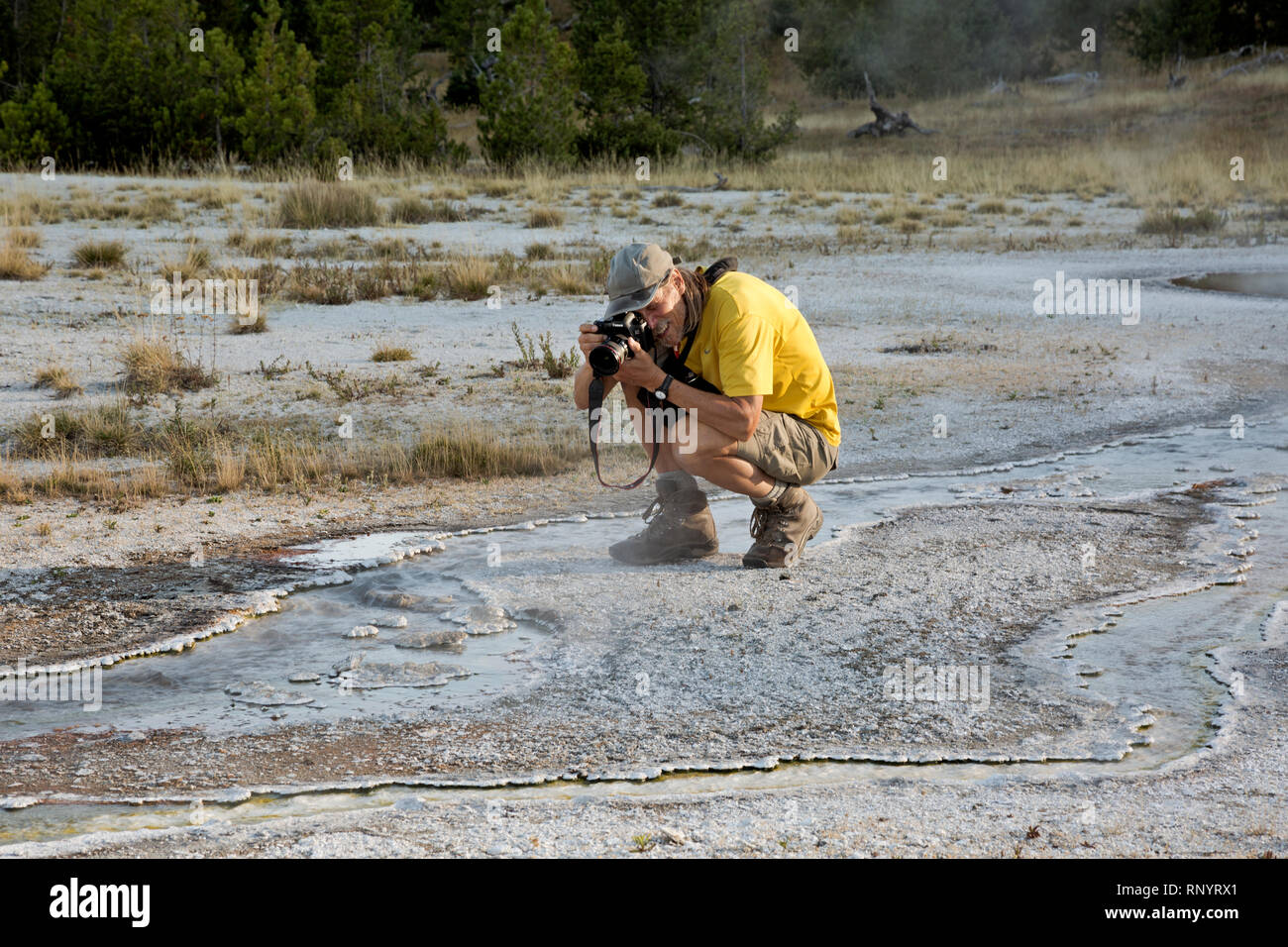 WY03826-00...WYOMING - Tom Kirkendall photographing the patterns created by the bulbous sinter along a runoff creek from a hot spring at the Rustic Gr - Stock Image