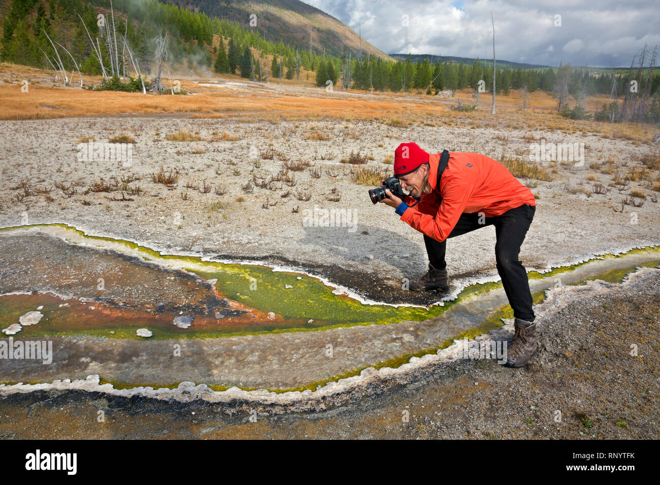 WY03836-00...WYOMING - Tom Kirkendall photographing the runoff from a hot spring in the Rustic Group area of the Heart Lake Thermal Area in the backco - Stock Image