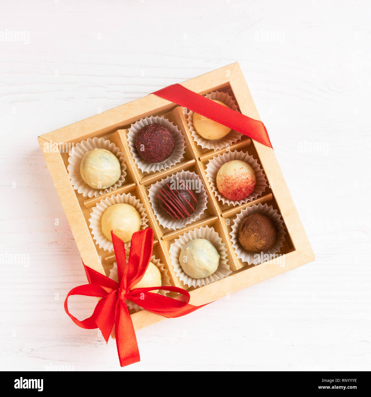 A gift set of various candies in a crafting box is decorated with a red satin ribbon. Festive concept. Flat layout. - Stock Image