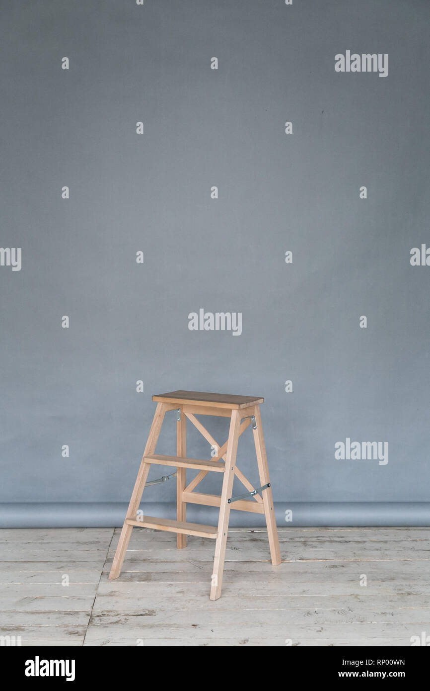 The working space of the photo studio with a grey paper background and chair. - Stock Image