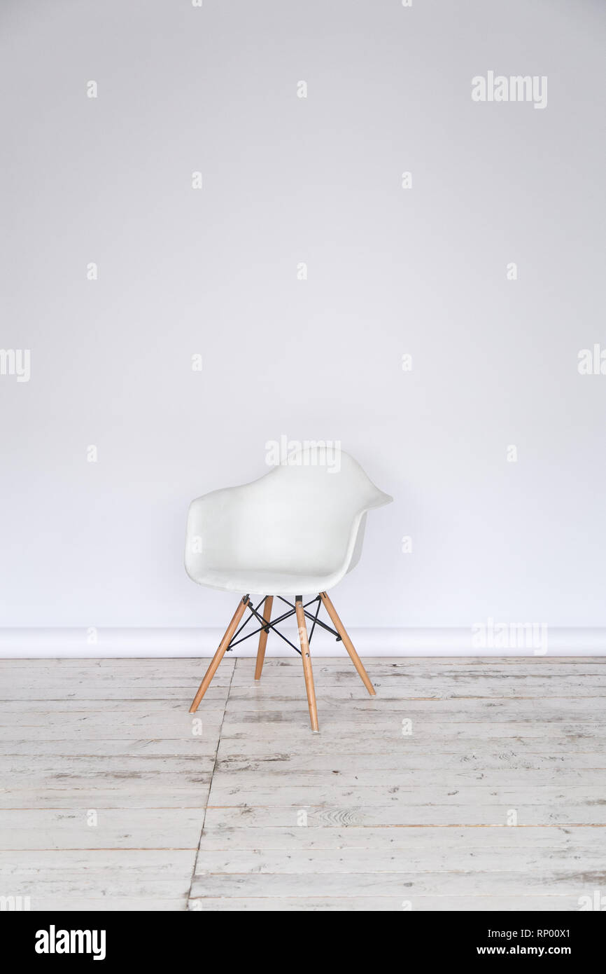 The working space of the photo studio with a white paper background and chair. - Stock Image