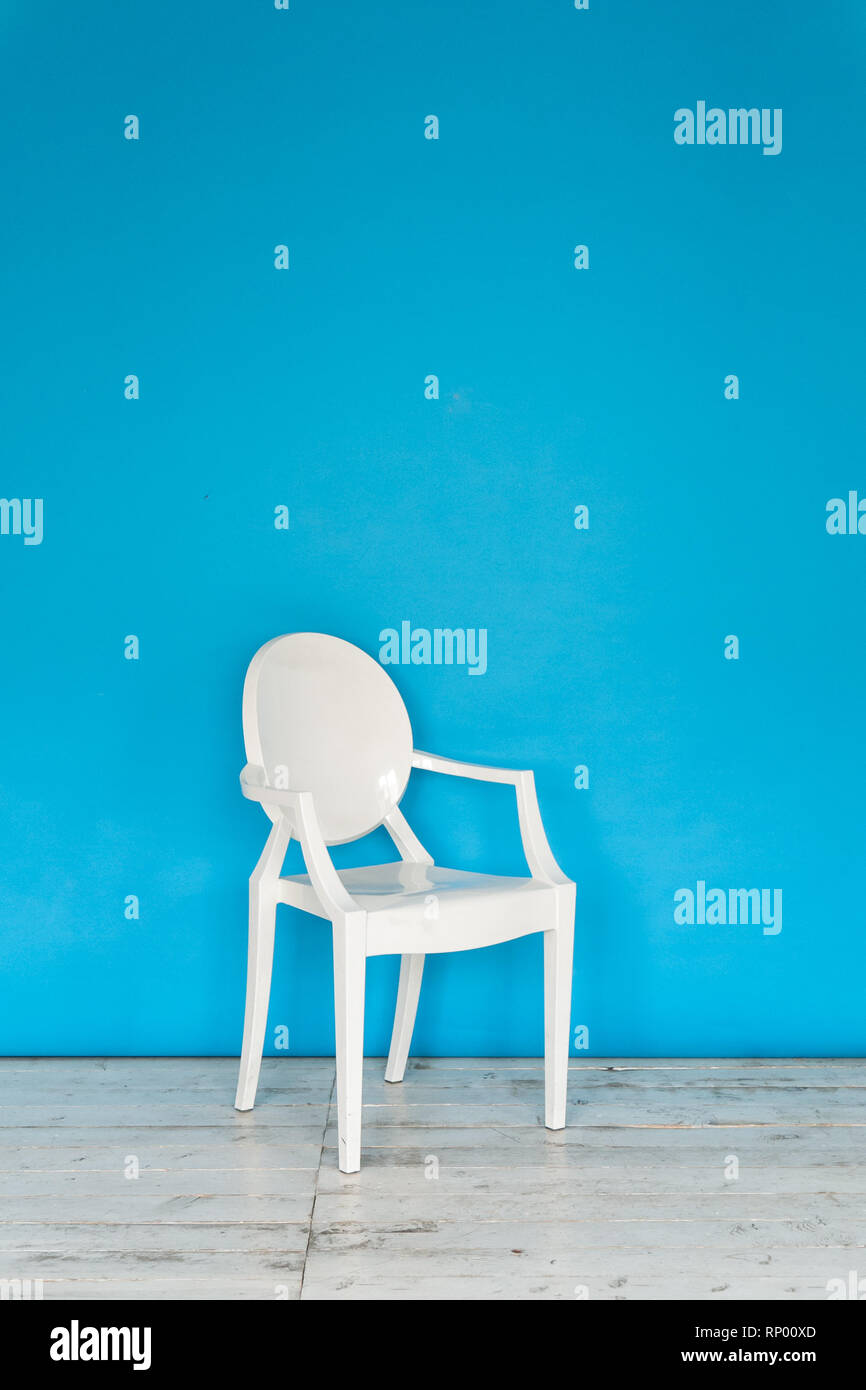 The working space of the photo studio with a blue paper background and chair. - Stock Image