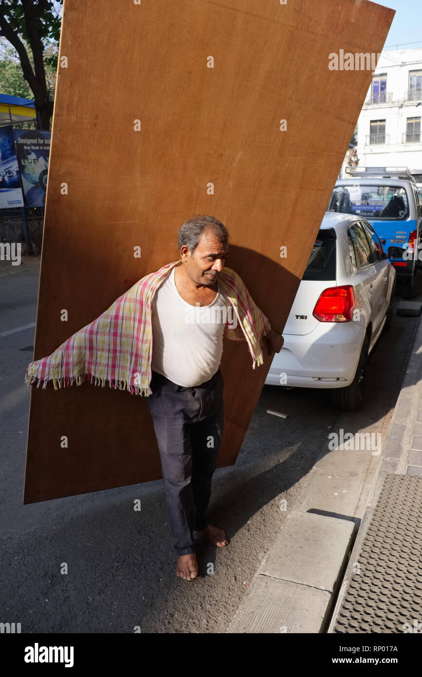 A barefoot carpenter in Mumbai, India, about to carry a think wooden plank, estimated to weigh 50 kilos, up several floors in a building - Stock Image