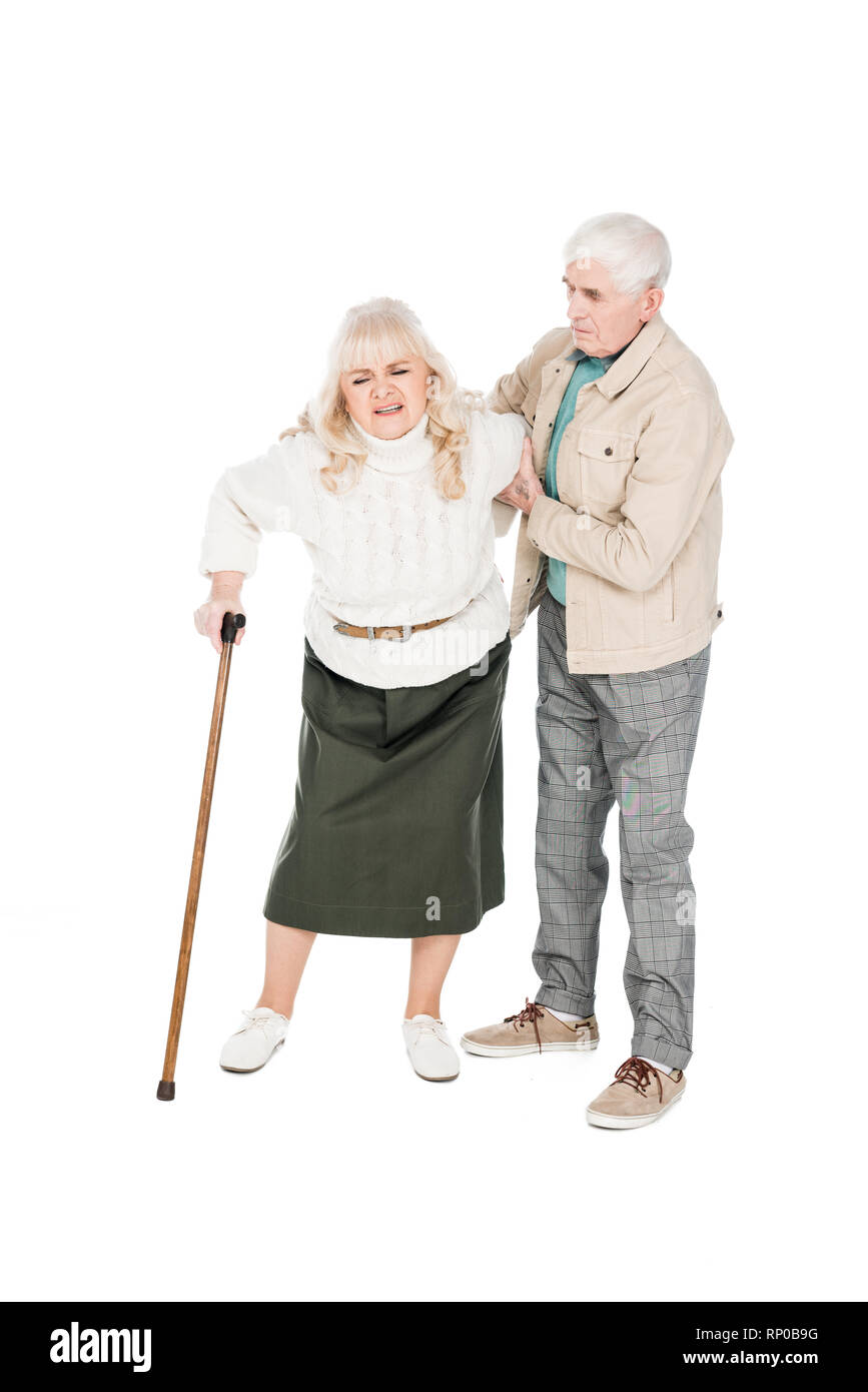 senior woman holding back while having arthritis pain and standing with caring husband isolated on white - Stock Image