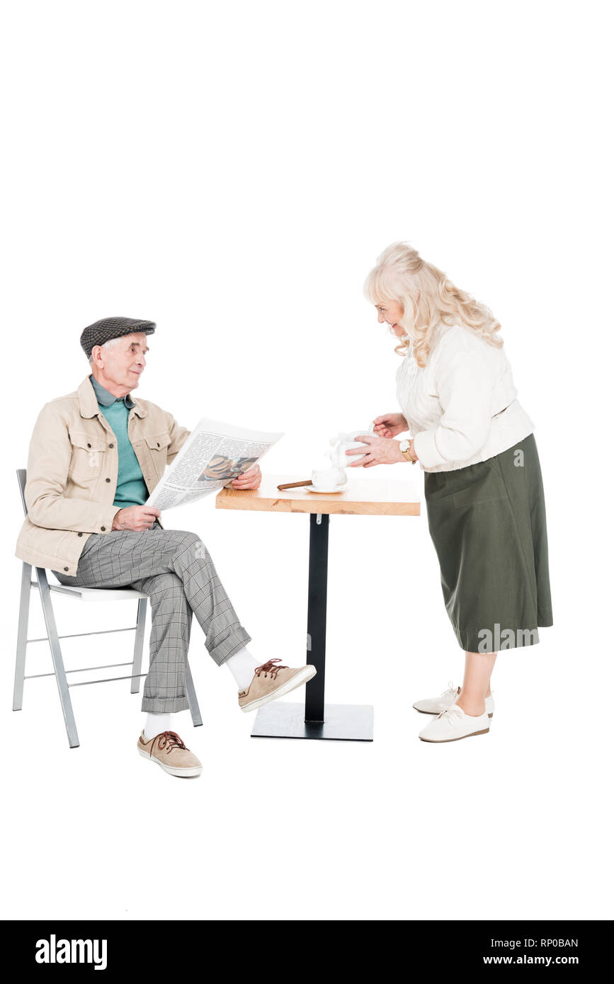 retired woman looking at husband with newspaper while pouring tea in cup isolated on white - Stock Image