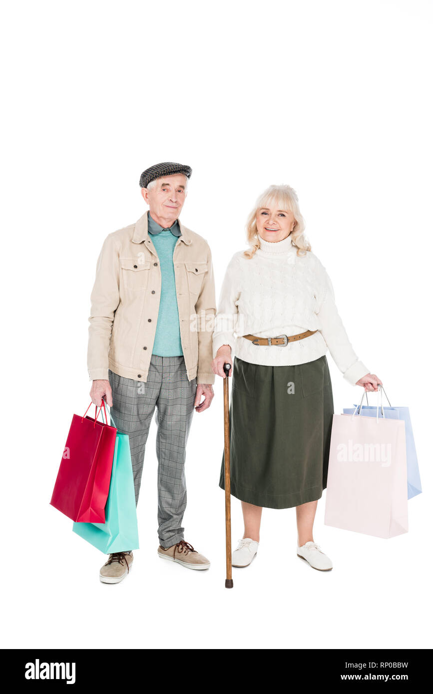 cheerful retired couple standing with shopping bags isolated on white - Stock Image