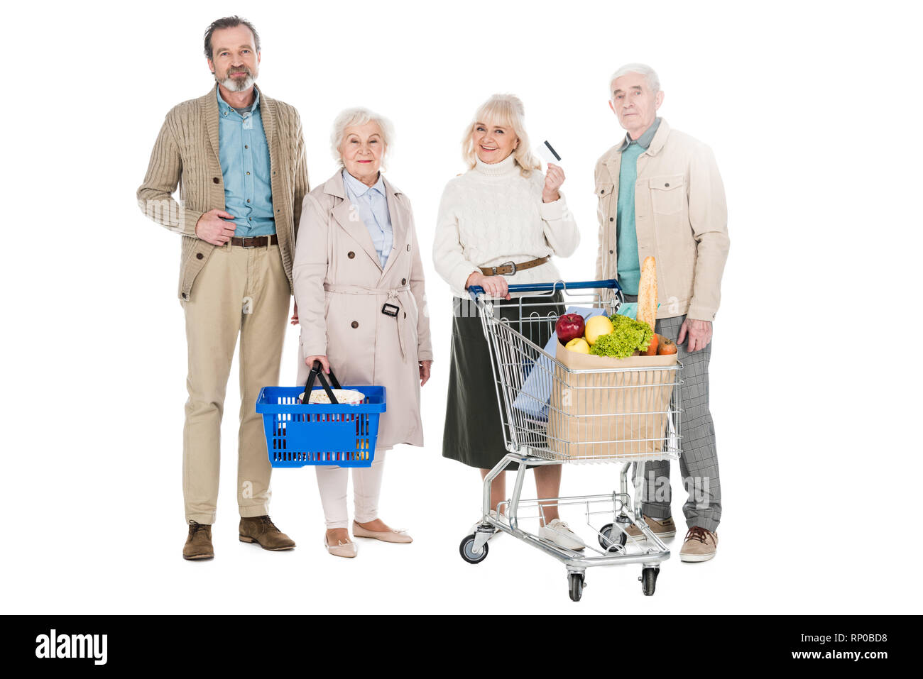 cheerful senior friends standing with basket and shopping cart isolated on white - Stock Image