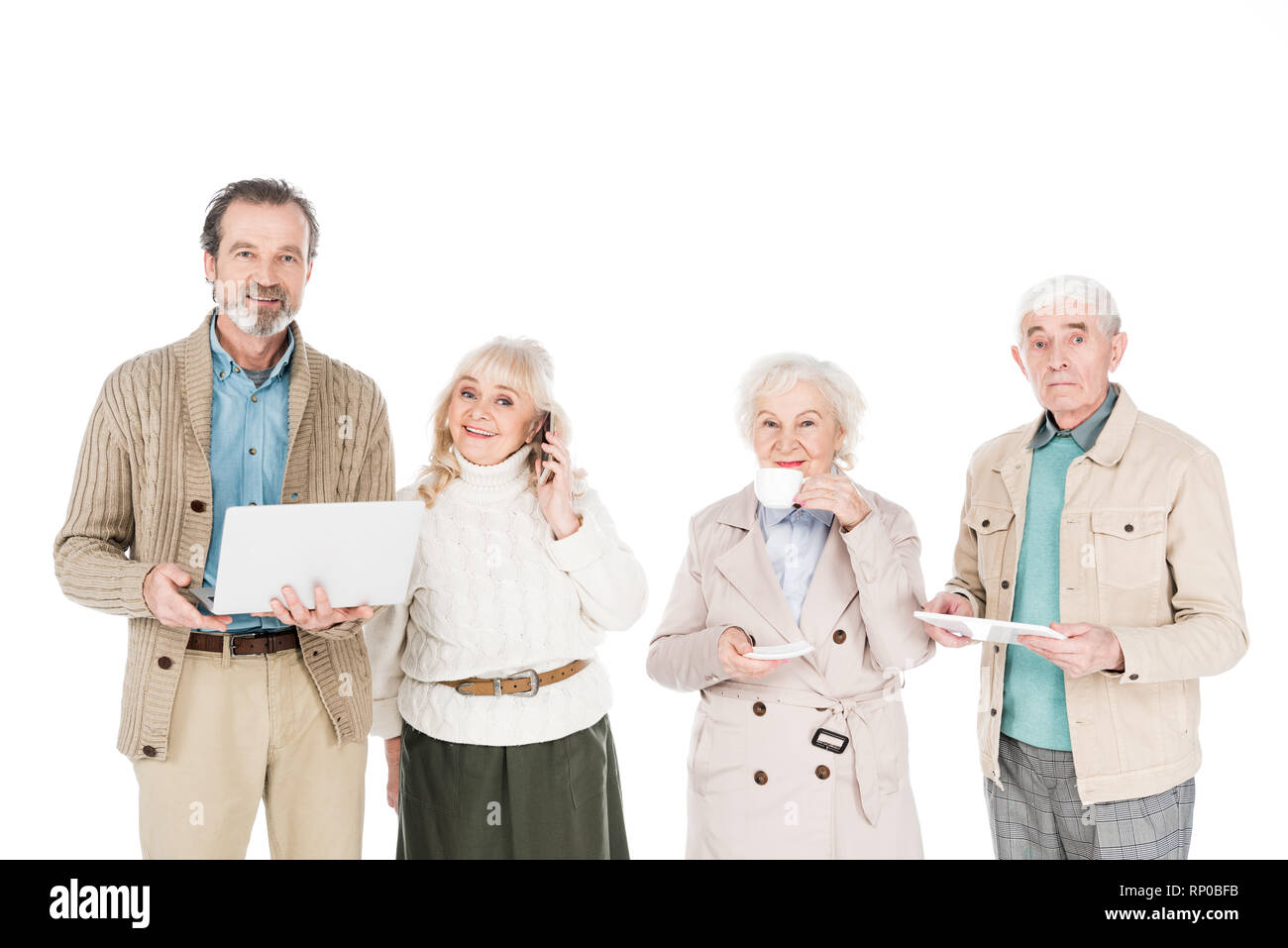 senior people standing with gadgets near woman drinking tea from cup isolated on white - Stock Image