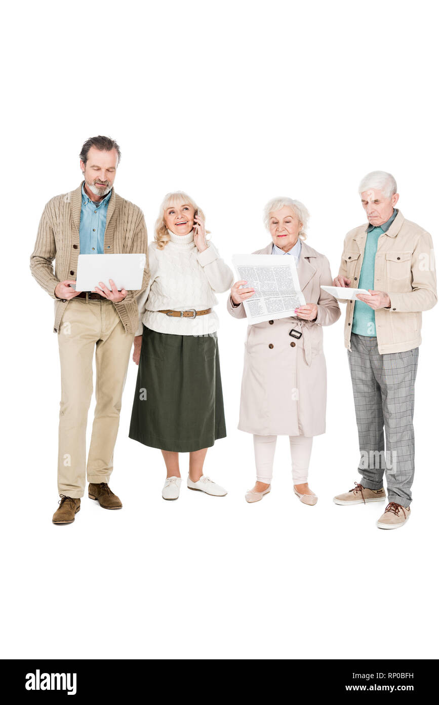 senior people standing with gadgets near woman reading newspaper isolated on white - Stock Image