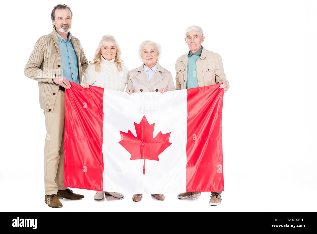 happy senior people holding flag of canada isolated on white - Stock Image