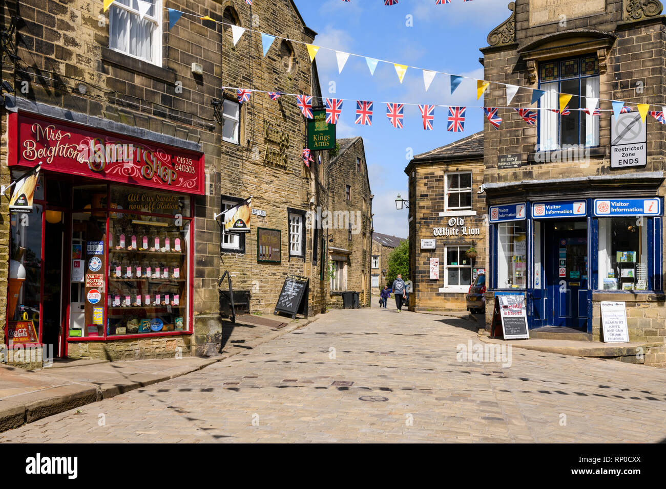 Traditional sweet shop, historic inns, Tourist Information & bunting over cobbled road - Main Street, Haworth village, West Yorkshire, England, UK. - Stock Image