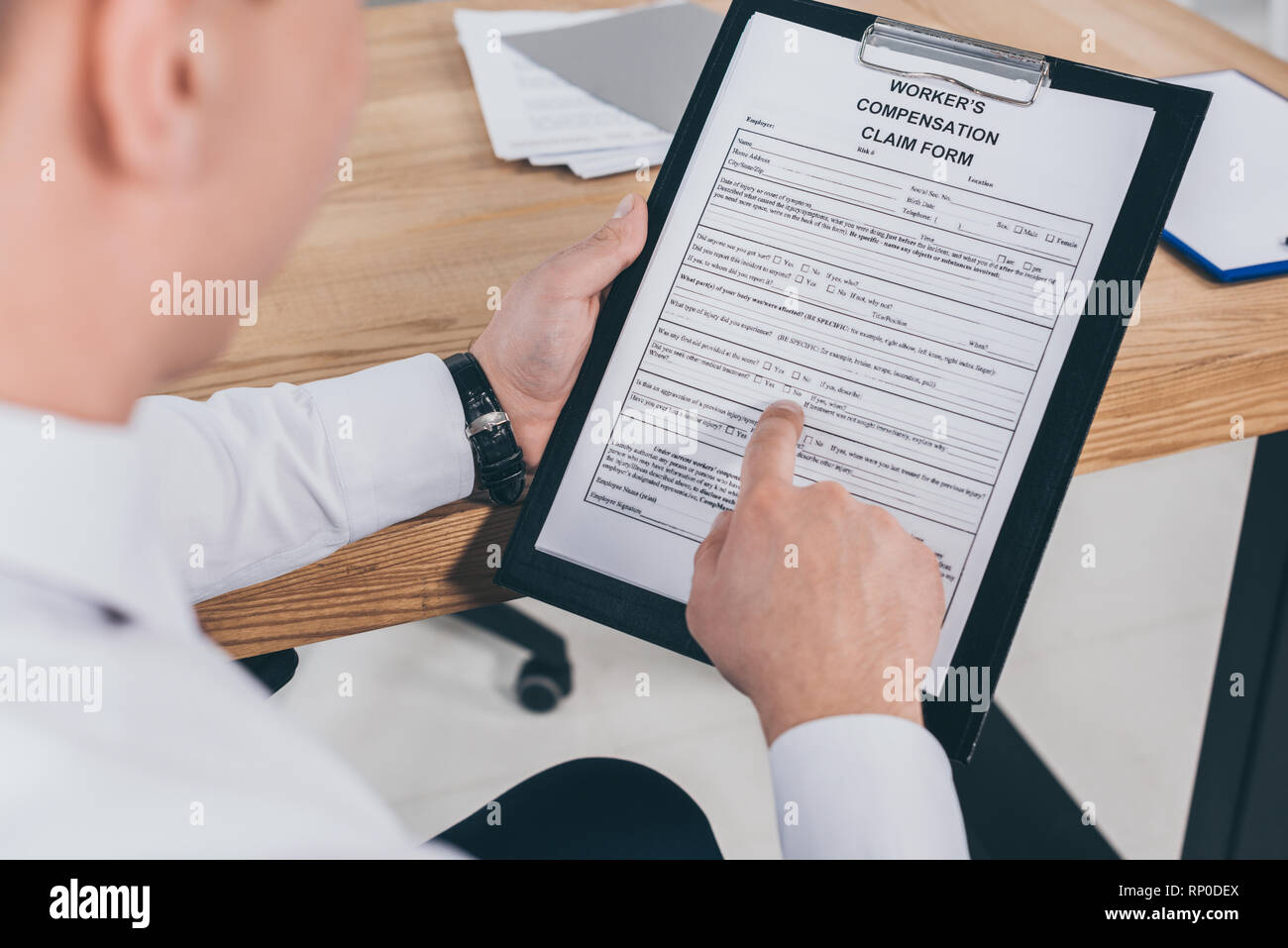 cropped view of businessman reading compensation claim form - Stock Image