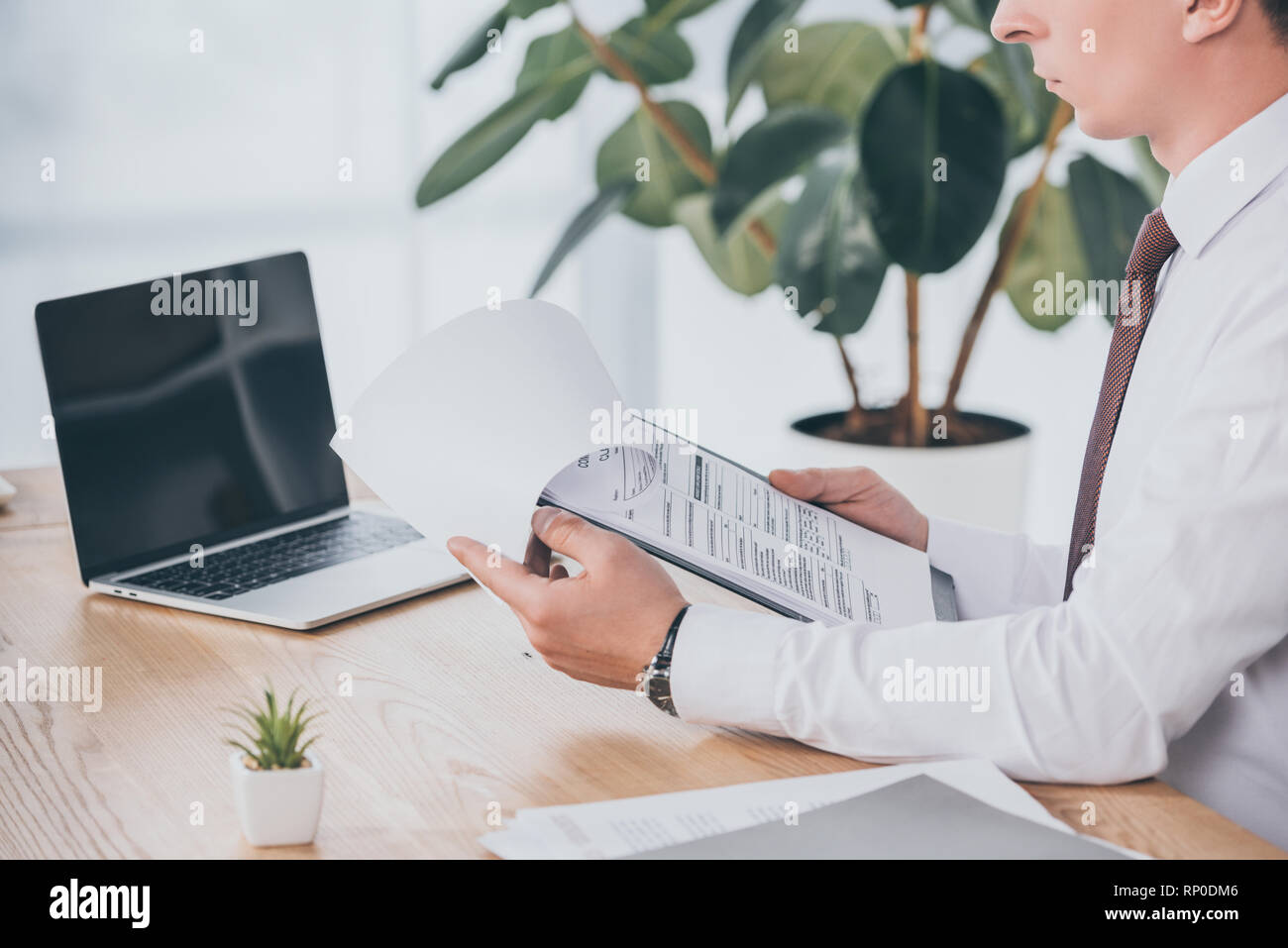 cropped view of businessman reading compensation claim at workplace - Stock Image