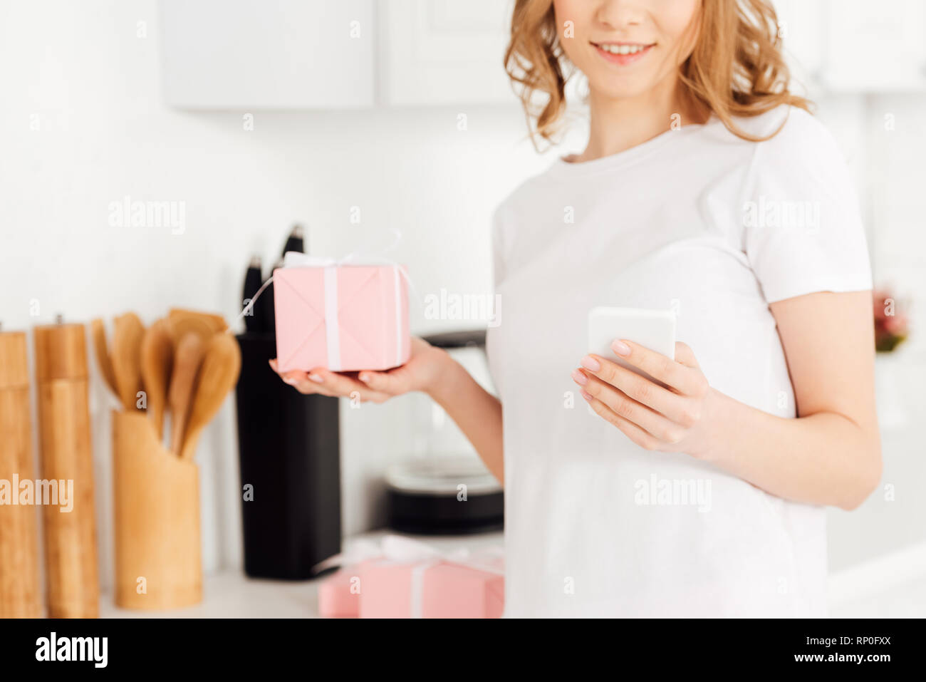 cropped view of girl in pajamas with gift box using smartphone in kitchen - Stock Image