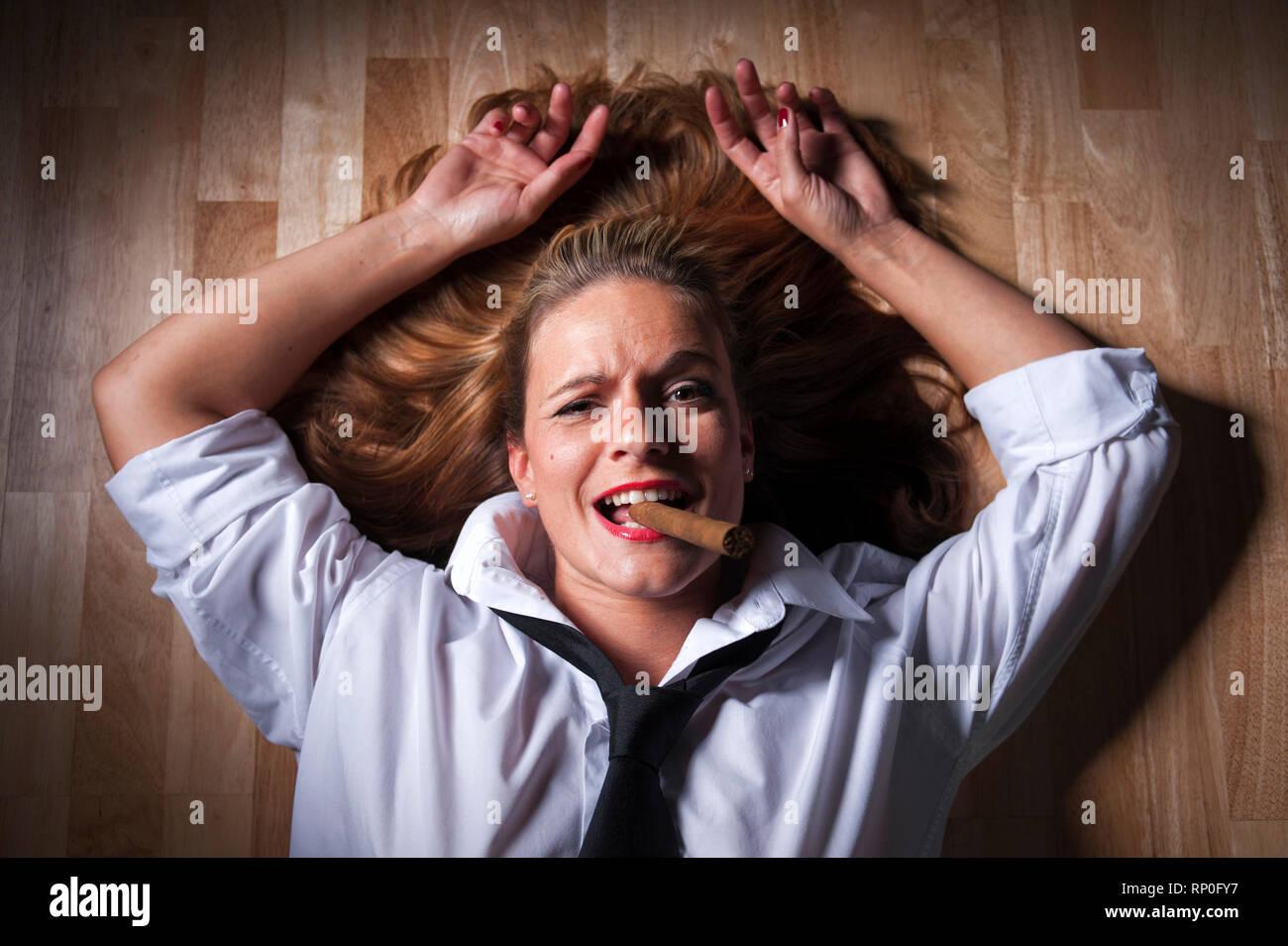 Dunkelblonde Frau mit ausgebreiteten Haaren liegt rauchend auf dem Boden. Sie traegt ein weisses Maennerhemd und eine schwarze Krawatte. MR:YES PR:YES - Stock Image