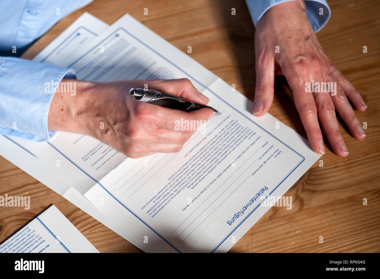 Frauenhaende die eine Patientenverfuegung ausfuellen auf einem Tisch mit einer Teetasse MR: yes PR: Yes - Stock Image