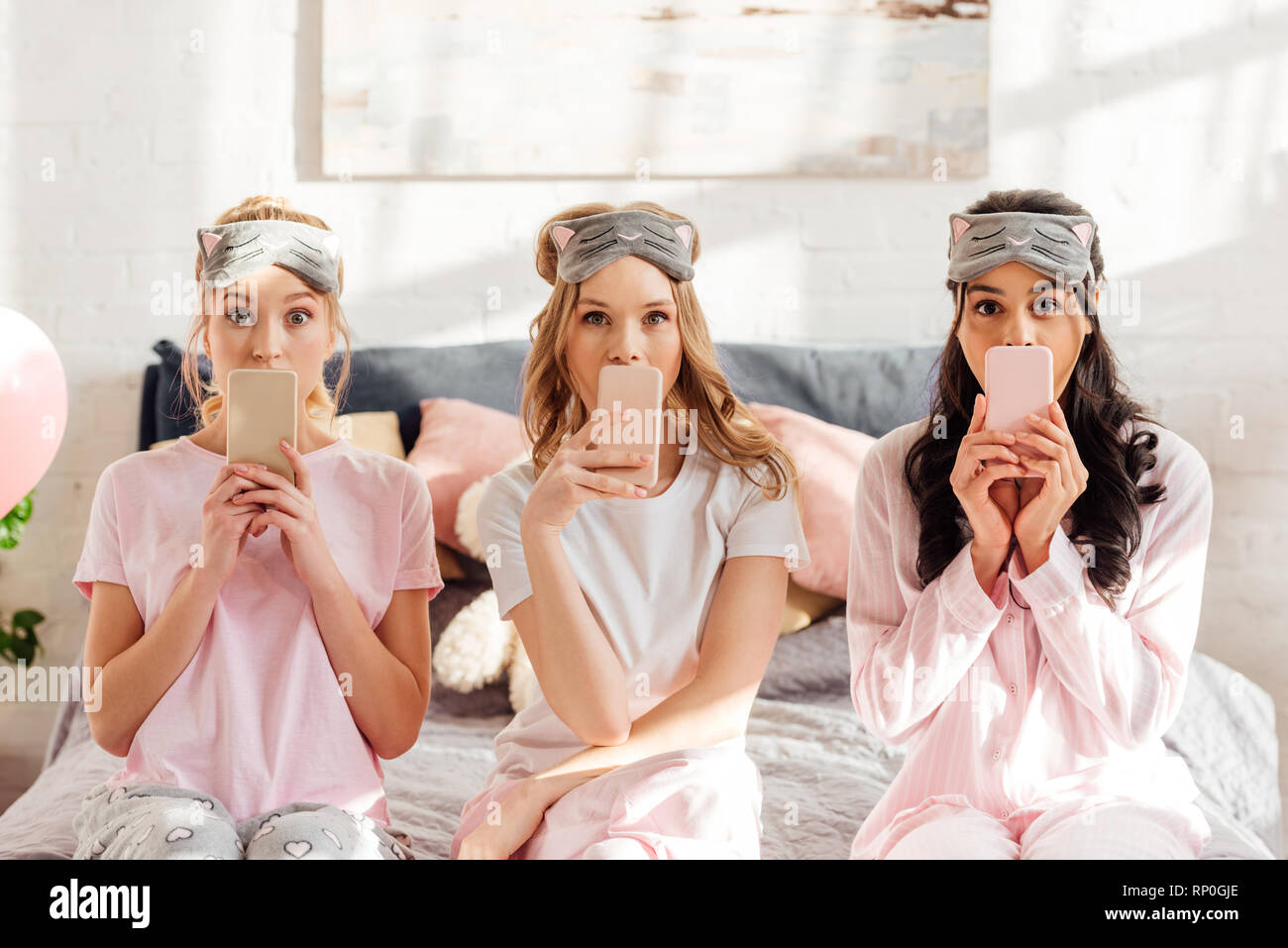 beautiful multicultural girls in sleeping masks sitting on bed and covering mouths with smartphones during pajama party - Stock Image