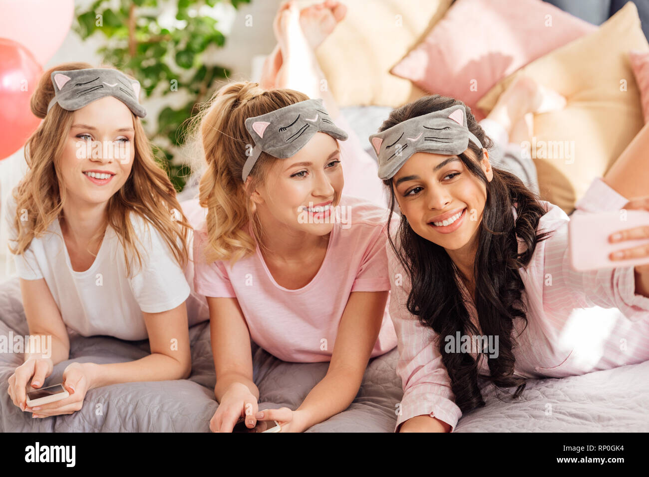 beautiful smiling multicultural girls in sleeping masks lying in bed and taking selfie on smartphone during pajama party - Stock Image