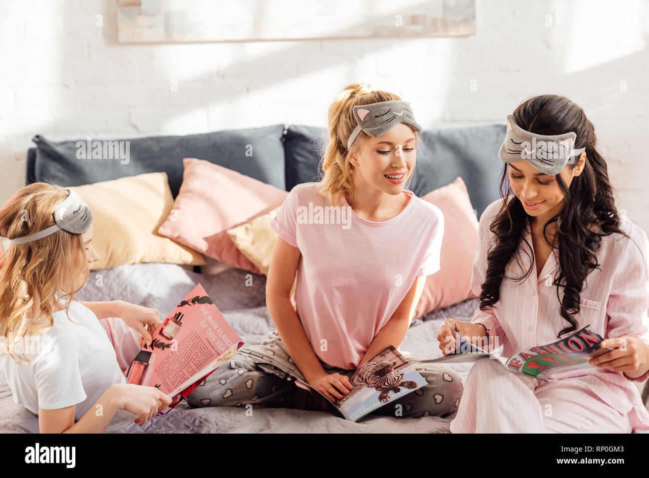 beautiful multicultural girls in sleeping masks reading magazines during pajama party - Stock Image